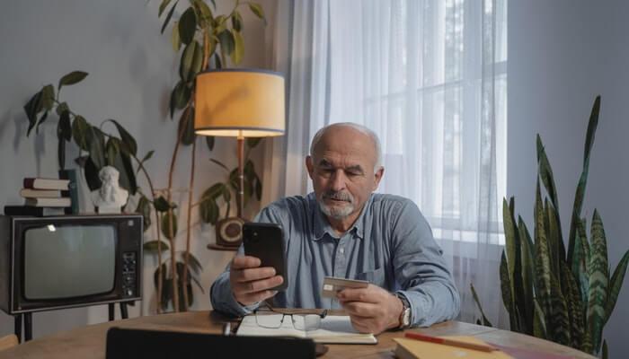 Homem idoso sentado à mesa mexe no celular com cartão de crédito na outra mão, representando o que é ecommerce
