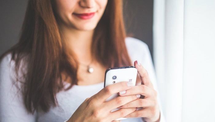 Mulher usando celular para navegar na internet
