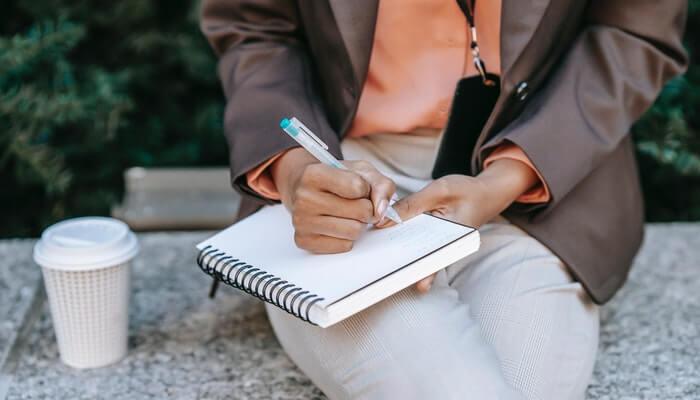 Mulher escreve em caderno nomes de empresa para registrar