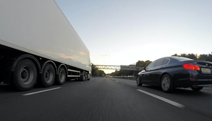 Caminhão e carro em estrada, representando transportadora ou Correios