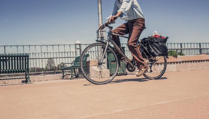 Pessoa andando de bicicleta por um caminho, representando como avaliar uma empresa e seu caminho de sucesso