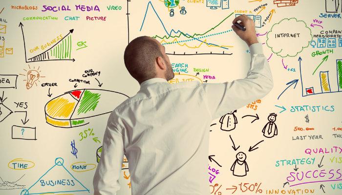 Homem escreve em lousa representando a análise PESTEL