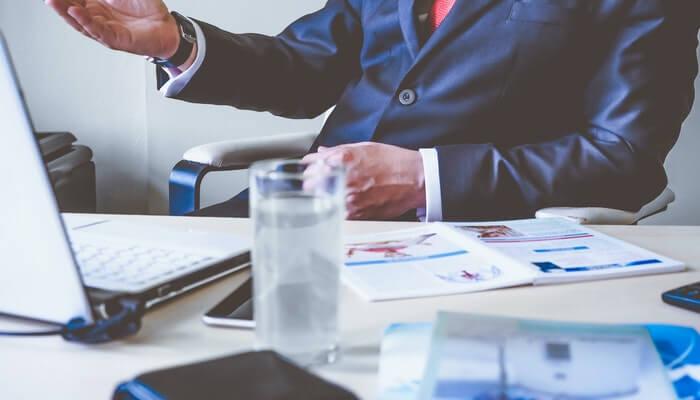 Homem de terno gesticula sentado em escrivaninha, em frente a computador, representando como usar o Google Analytics para decisões de negócio
