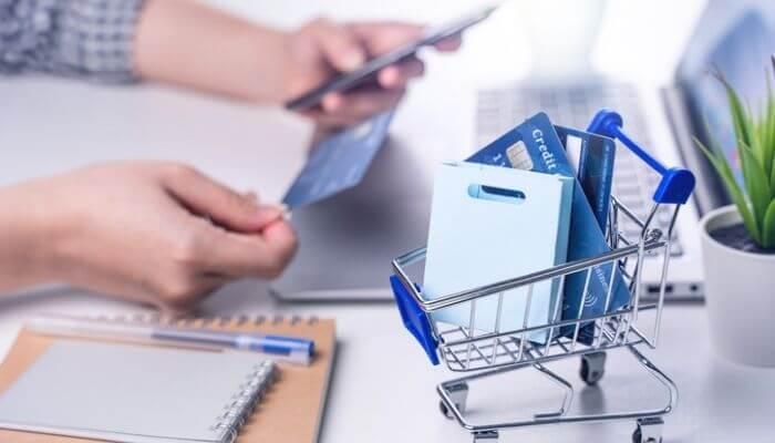 imagem mostra uma mão com cartão de crédito em frente a um computador, simulando o checkout de compra por um api de pagamento