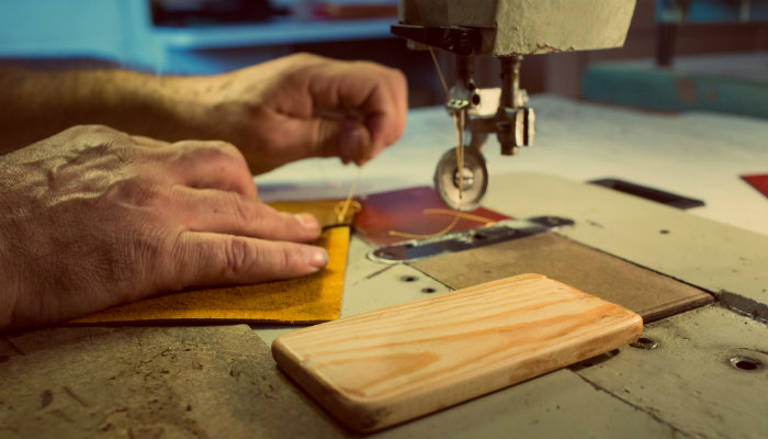 Mãos costuram em frente à máquina de corte, representando vender artesanato online