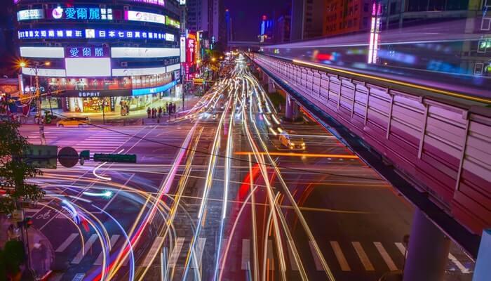 Rua com luzes de faróis de carros representa como aumentar tráfego do site