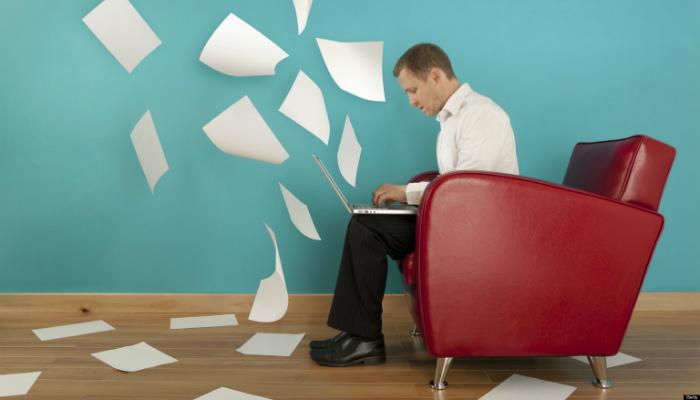 Homem digita em computador com folhas voando ao seu redor, representando como criar um blog no WordPress