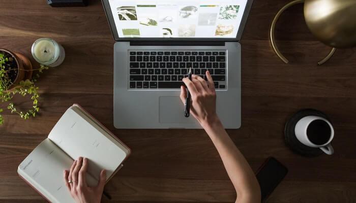Mulher mexe em computador e anota em caderno, representando como cadastrar domínio