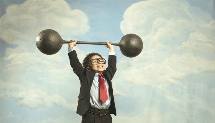 Criança de terno e óculos levanta peso de academia, representando a rentabilidade da empresa