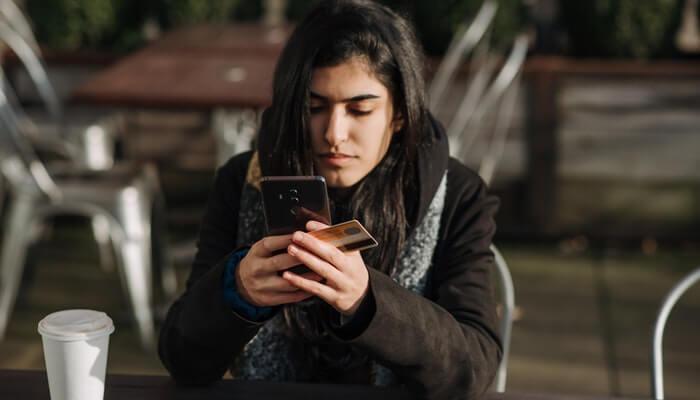 Mulher mexe no smartphone com cartão de crédito na mão, representando o checkout transparente do PagSeguro