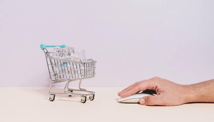 Mão mexe em mouse ao lado de miniatura de carrinho de compras, representando o checkout