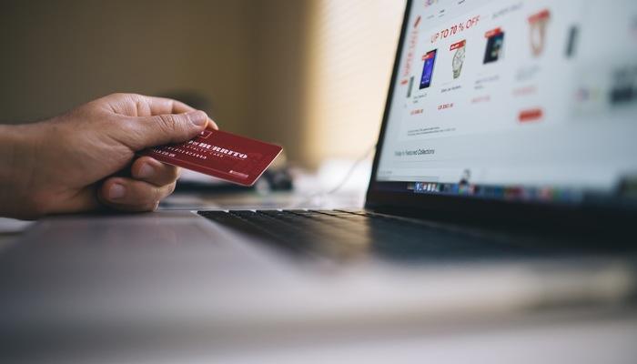 Mão segura cartão de crédito em frente a computador, representando como cobrar pelas vendas online
