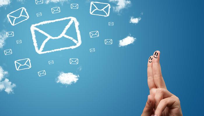 Dedos com desenhos de rostos felizes ao lado de nuvens em formato de envelopes, representando o e-mail marketing