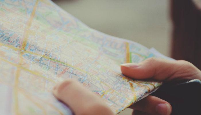 Mãos segurando mapa representam como elaborar um plano de ação