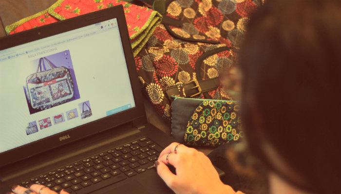 Mulher olha bolsa em página de produto online