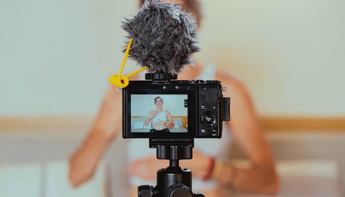 Mulher fala para câmera e aparece no visor do aparelho, representando como fazer live