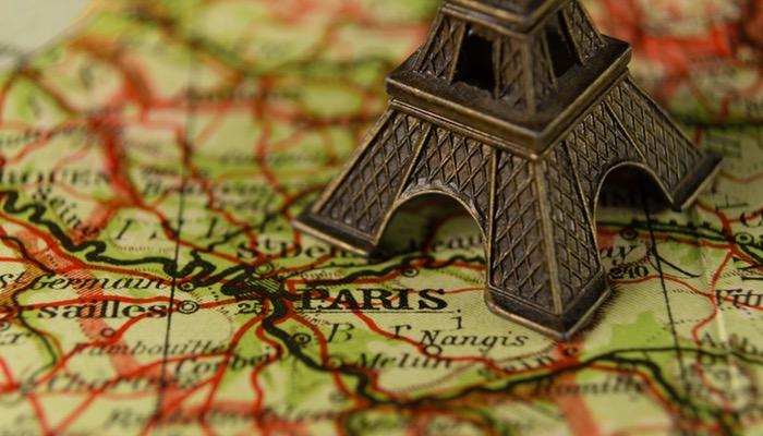 Miniatura de Torre Eiffel sobre mapa representa como ganhar dinheiro viajando