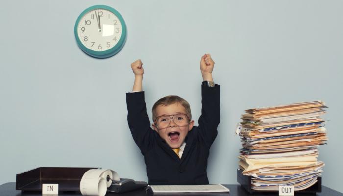 Menino com pose de comemoração em mesa de trabalho, representando como gerenciar tarefas