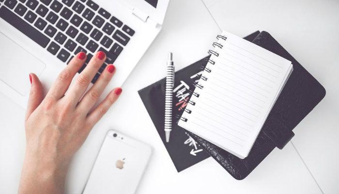 Mão de mulher em notebook, com smartphone e caderno ao lado, representa cronograma de postagens no Facebook