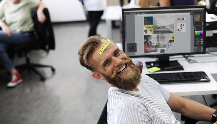 Homem sorri em escritório descontraído, com adesivo escrito 'be happy' na testa, representando a cultura empresarial