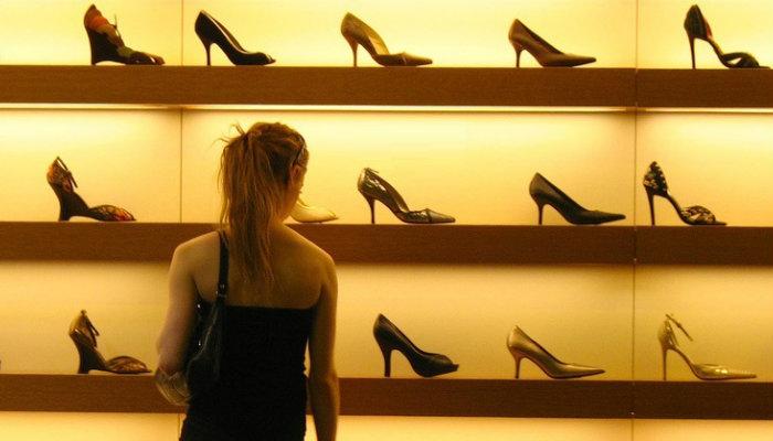 Mulher tomando decisão de compra em frente a vitrine de sapatos
