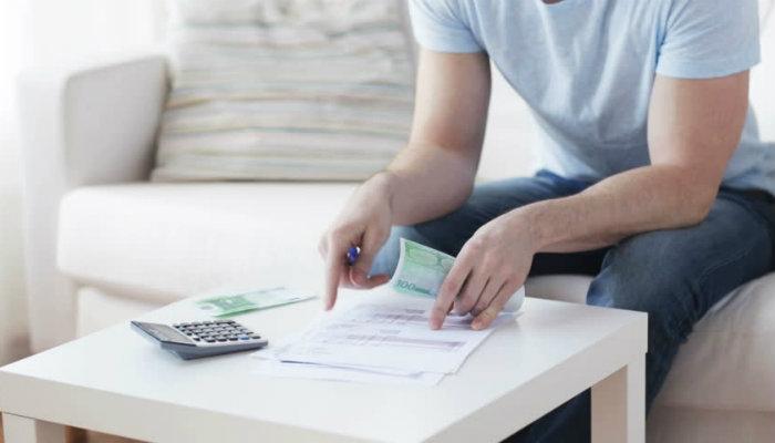 Homem lê papel, em mesa com cédulas e calculadora, representando o diagnóstico financeiro