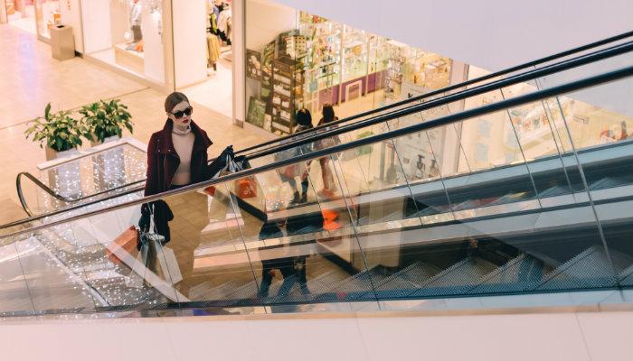 Mulher com sacolas em escada rolante de shopping representa as dicas para loja virtual de roupas