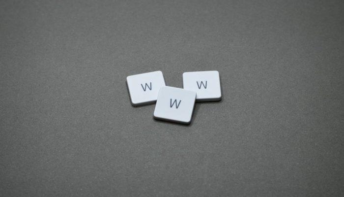 tres fichas blancas con la letra w sobre superficie gris