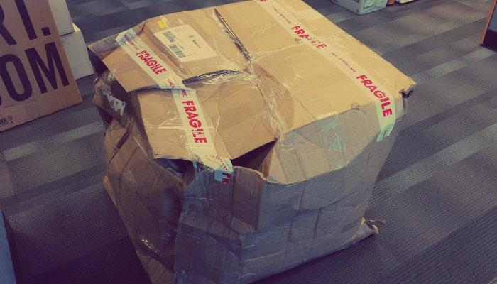 Caixa de papelão toda amassada representa embalagem danificada nos Correios