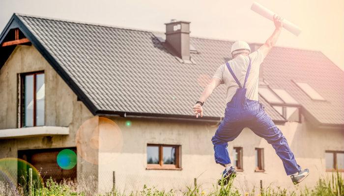 Homem com projeto na mão pula feliz em frente a casa, representando o empreendedor de sucesso