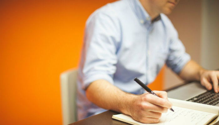 Homem escrevendo em um caderno, representando o planejamento do empreendedorismo digital