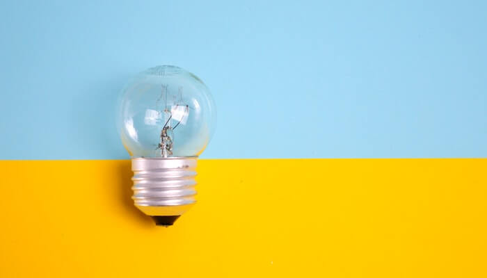 Lâmpada sobre fundo azul e amarelo representa a ferramenta do Facebook Insights