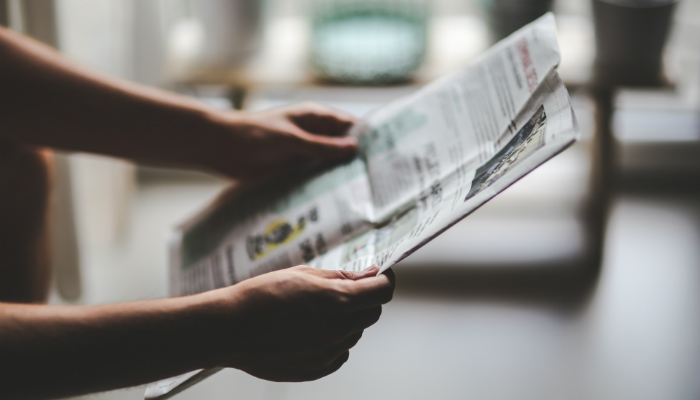 Mãos segurando jornal, representando pessoa buscando fornecedores de produtos importados no Brasil