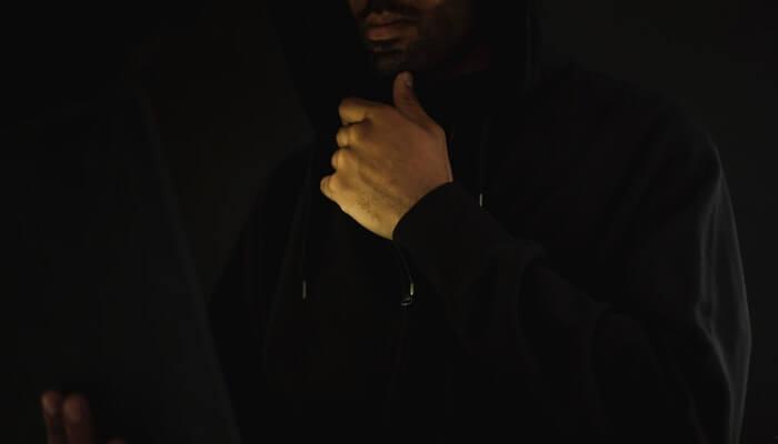 Homem mexe em computador de capuz, representando a fraude no ecommerce