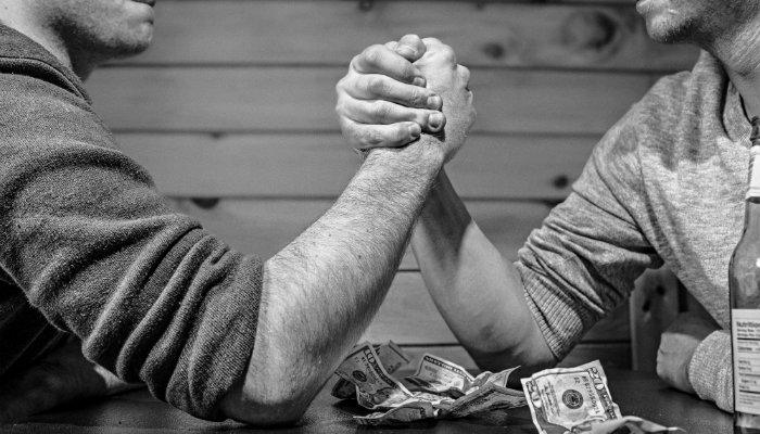 Homens em disputa de braço de ferro, representando Google Ads versus Facebook Ads