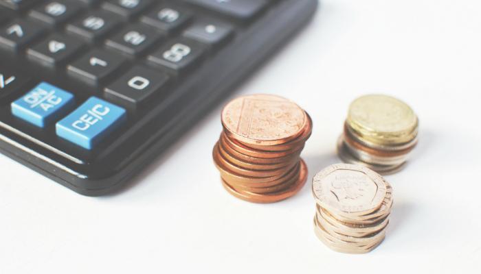 Calculadora e moedas representam os impostos sobre importação