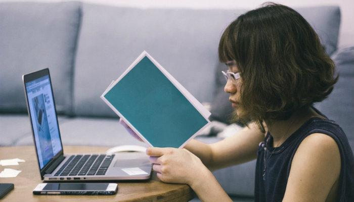 Garota lendo conteúdos na internet, representando Inbound e Outbound Marketing