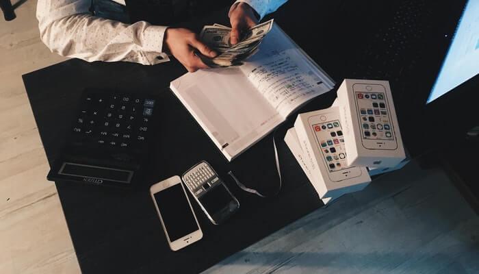 Homem conta dinheiro sobre mesa, representando indicadores financeiros
