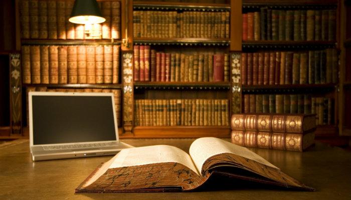 Livro e computador em mesa de biblioteca representam o jurídico no e-commerce