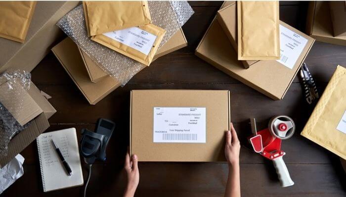 Mãos embalam caixa para envio, representando a plataforma Kangu