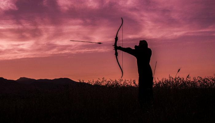 Homem lançando flecha no alvo distante , representando o lançamento de produtos