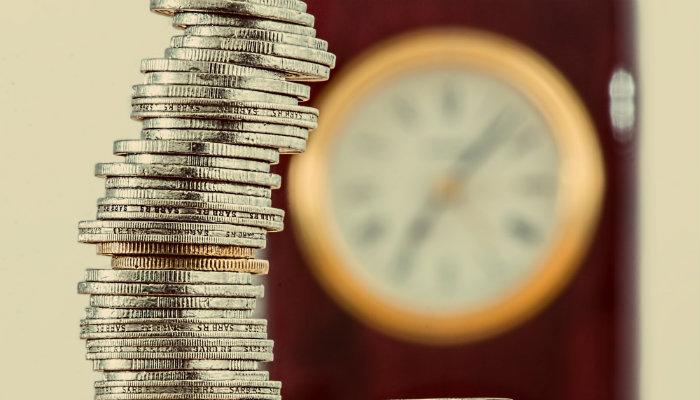 Pilha de moedas em frente a relógio, representando quando e como lançar um produto no mercado