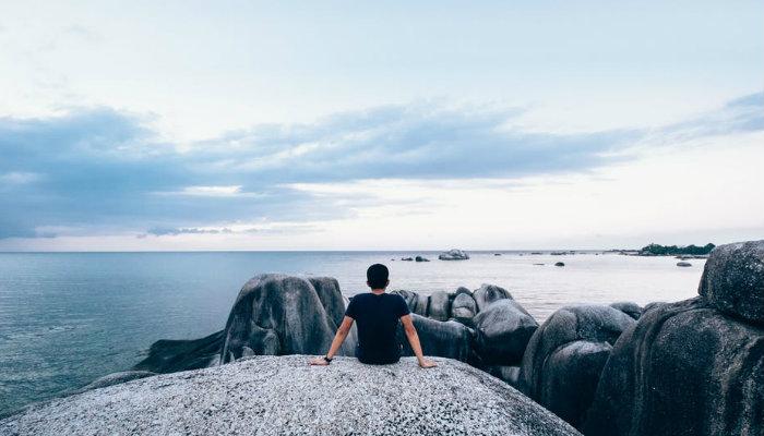 Homem observa o horizonte na praia, representando as lições do livro Essencialismo