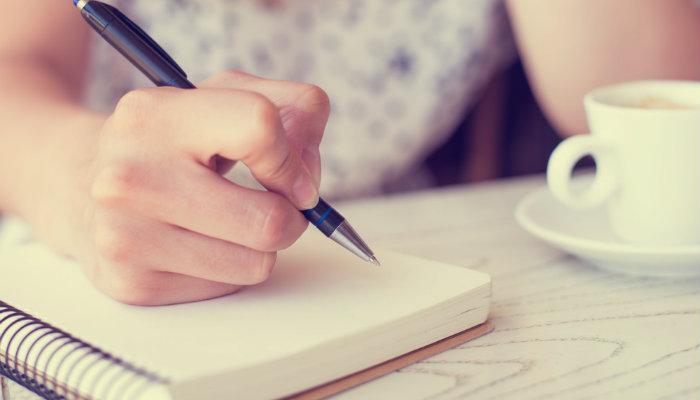 Mão escreve em caderno, como quem anota como fazer listas de remarketing no Google