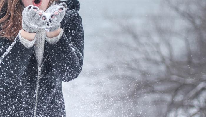 Mulher assopra neve em suas mãos, representando a loja virtual no Natal
