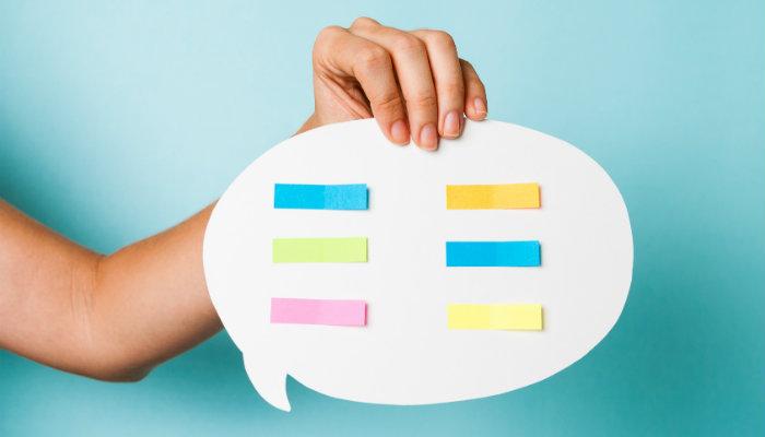 Mão segura papel em formato de balão de fala com post its coloridos, representando o os conteúdos para Facebook