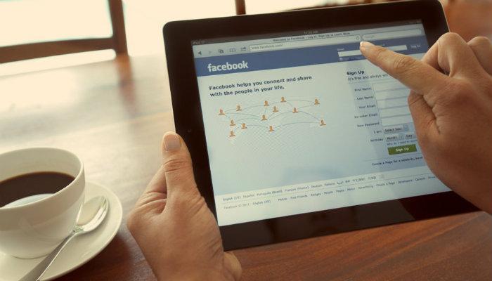 Mulher mexendo no Facebook em tablet