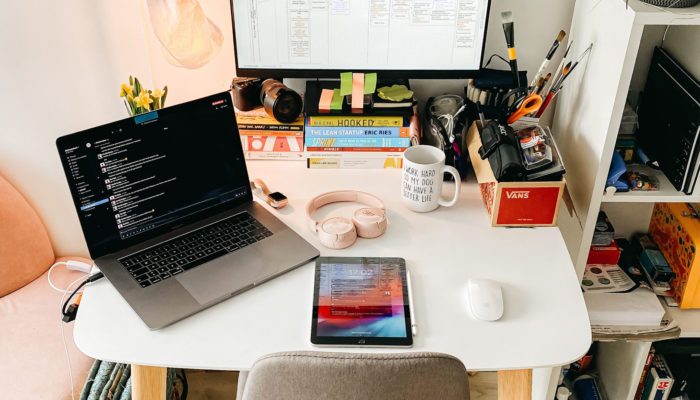 Escritorio en casa con material de trabajo, laptop, tablet y pantalla