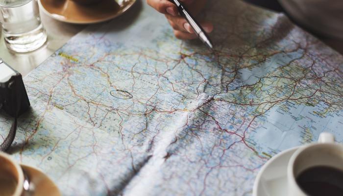Mão segura caneta sobre mapa, representando os nômades digitais