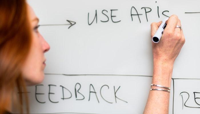 Imagem mostrando uma mulher escrevendo em uma lousa sobre o que é API.